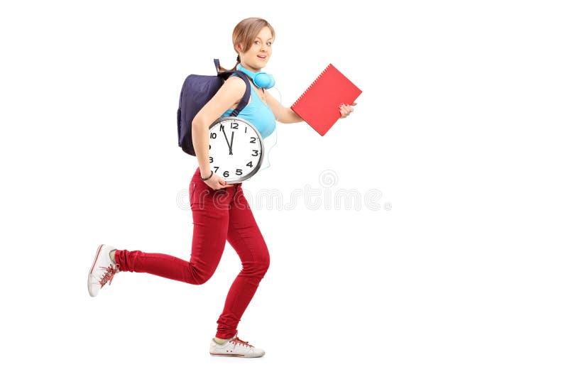 Portrait intégral d'une étudiante avec l'horloge tard pour le cla photos libres de droits