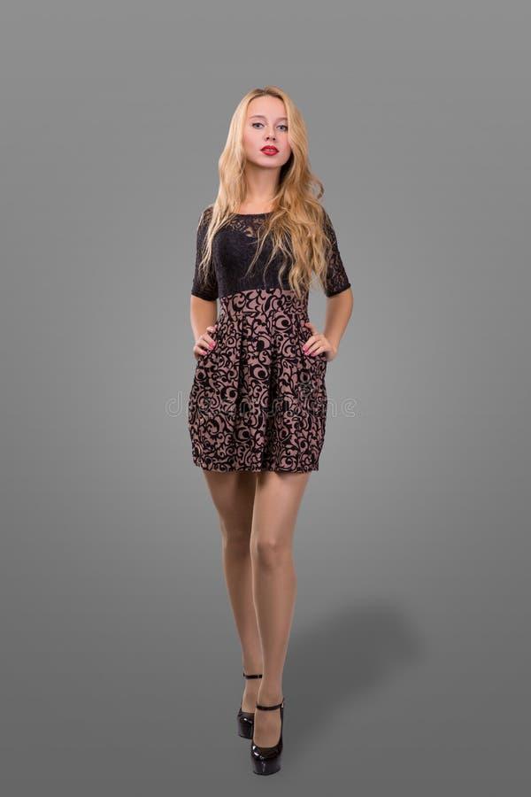 Portrait intégral d'une belle femme blonde dans peu de robe noire de mode Fond gris photographie stock
