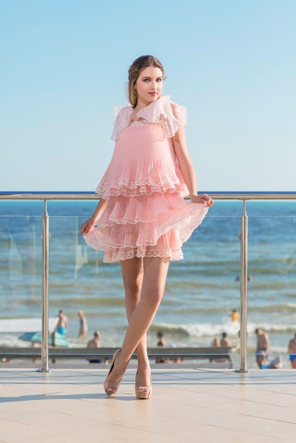 Portrait intégral d'une femme avec du charme dans une robe rose avec des ruches sur le fond d'une mer Plage, mer, et concept d'ét image libre de droits
