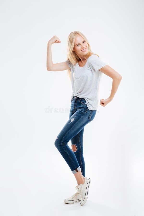 Portrait intégral d'une femme heureuse montrant ses muscles image libre de droits