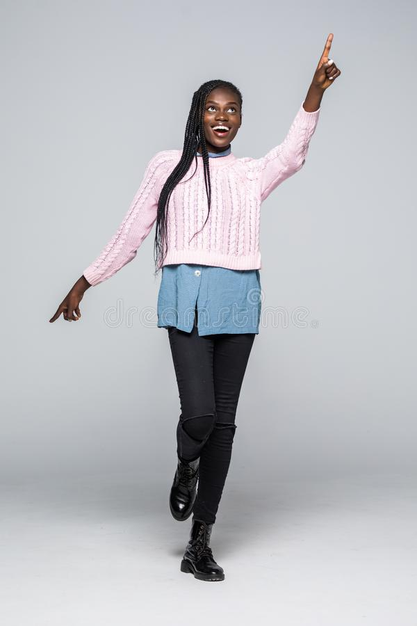 Portrait intégral d'une jeune femme africaine heureuse sautant et dirigeant le doigt à l'espace de copie au-dessus du fond gris photographie stock
