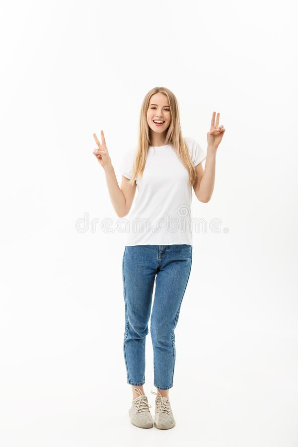 Portrait intégral d'une jeune femme heureuse tenant et montrant le geste de paix avec deux mains d'isolement au-dessus du blanc photographie stock