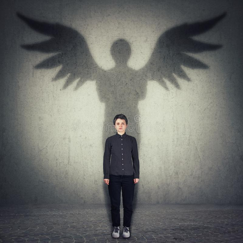 Portrait intégral de femme sûre occasionnelle moulant une ombre de super héros avec des ailes d'ange sur un mur de chambre noire  image stock