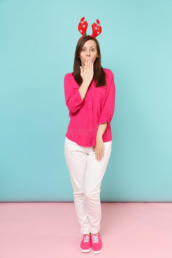 Portrait intégral de jeune femme d'amusement dans le chemisier rose de chemise, pantalon blanc, pose de klaxons de cerfs communs  photo libre de droits