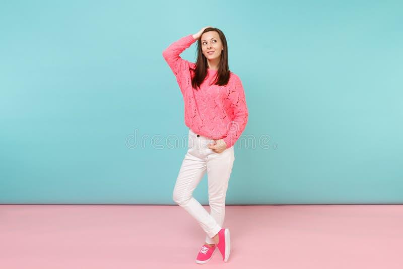 Portrait intégral de jeune femme de sourire dans le chandail rose tricoté, pose blanche de pantalon d'isolement sur le bleu rose  images stock