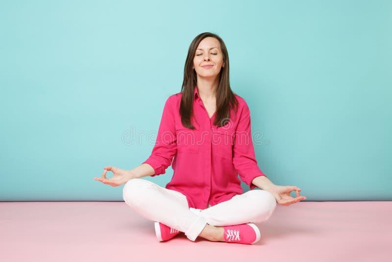 Portrait intégral de jeune femme de sourire dans le chemisier rose de chemise, pantalon blanc se reposant sur le plancher d'isole images libres de droits
