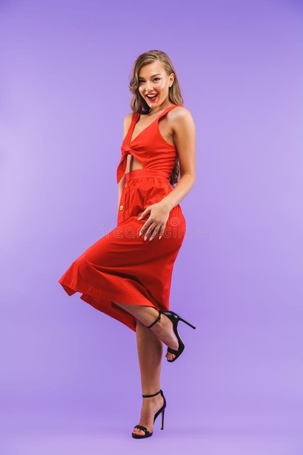 Portrait intégral de la jeune femme positive 20s portant le dre rouge photo libre de droits