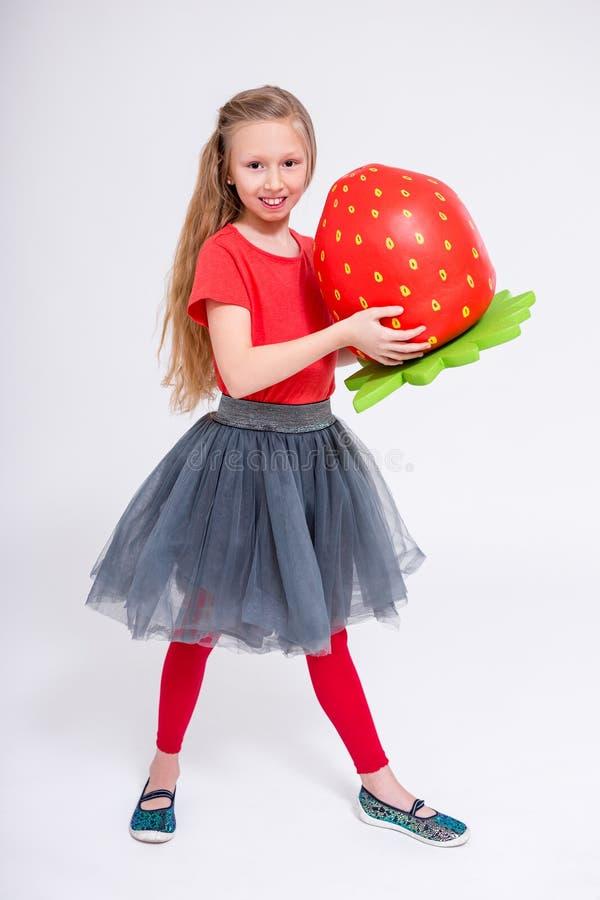 Portrait intégral de petite fille mignonne avec la grande fraise artificielle au-dessus du blanc images stock