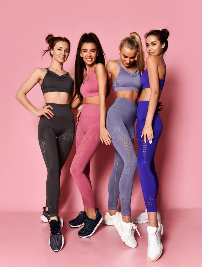 Portrait intégral de quatre amis internationaux de filles de sport posant sur le fond rose photographie stock libre de droits