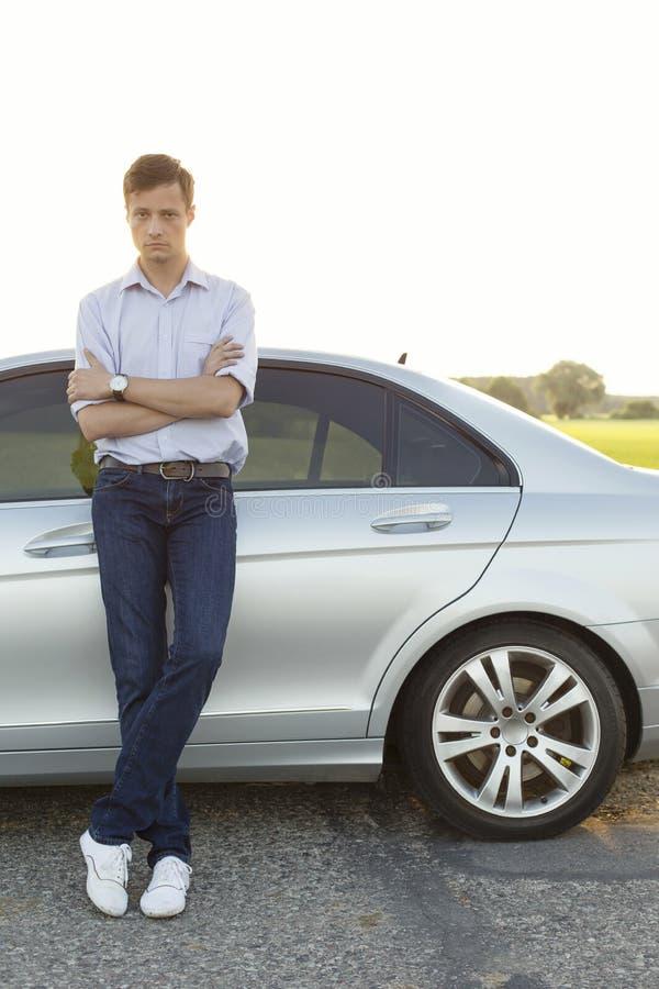 Portrait intégral de voiture se tenante prêt de jeune homme à la campagne photo stock