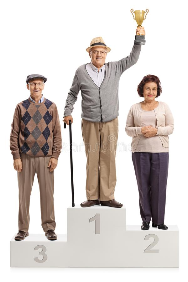 Portrait intégral des personnes supérieures sur le piédestal d'un gagnant pour le premier deuxième et troisième endroit photos libres de droits
