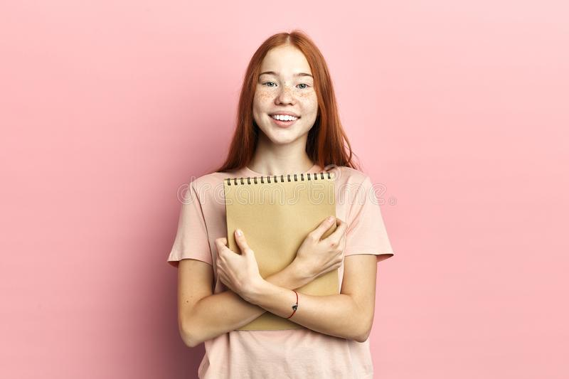 Portrait of intelligent cute clever happy female student with notebook stock photo