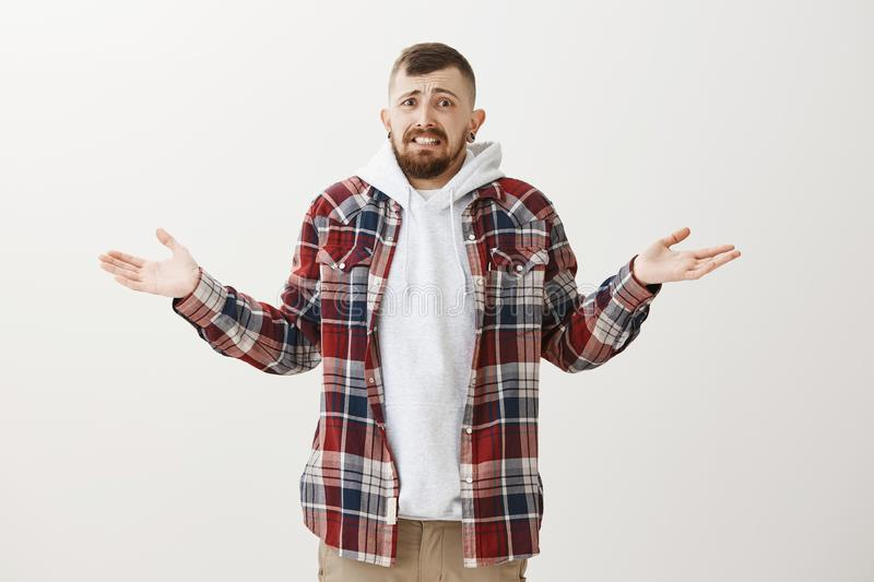 Portrait of intense clueless attractive bearded guy with stylish hairstyle, spread hands and shrugging, smiling awkwadly. With frowned eyebrows, being confused royalty free stock photography
