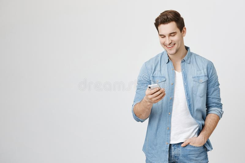 Portrait of interesting and handsome european man holding telephone while texting, isolated over white background royalty free stock images
