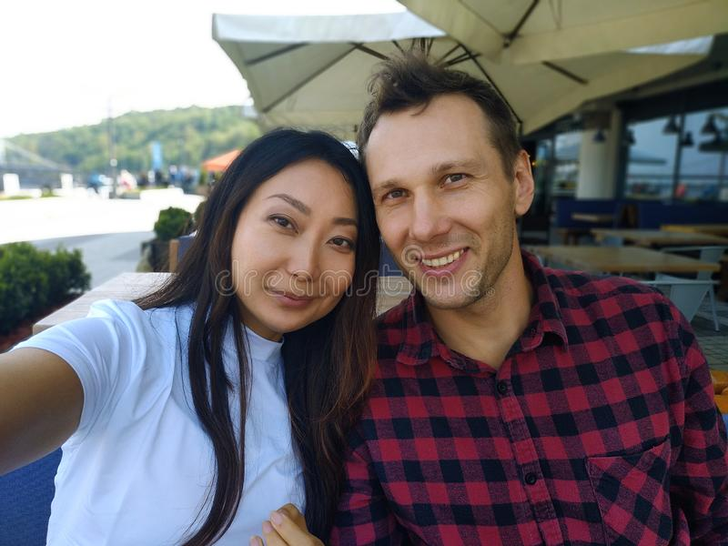 Portrait of a international couple in cafe smiling. European guy and asian woman at the bar taking selfie with mobile phone on holiday royalty free stock photos