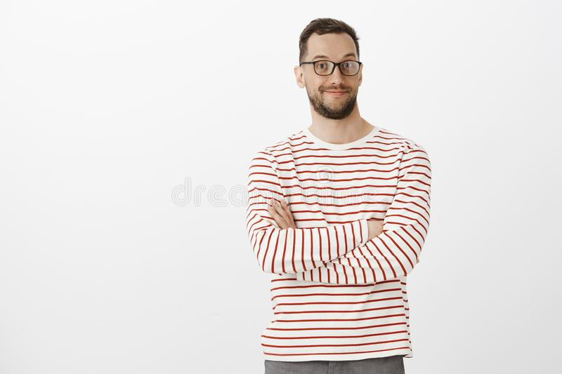 Portrait of intrigued pleasant handsome male in black glasses, smiling broadly, holding hands crossed on chest, smiling stock image