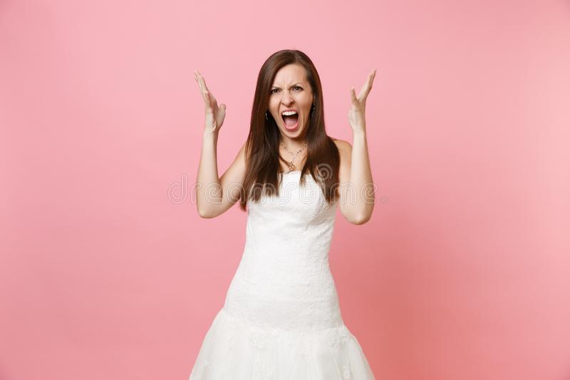 Portrait of irritated angry bride woman in beautiful white wedding dress stand screaming spreading hands isolated on stock photos