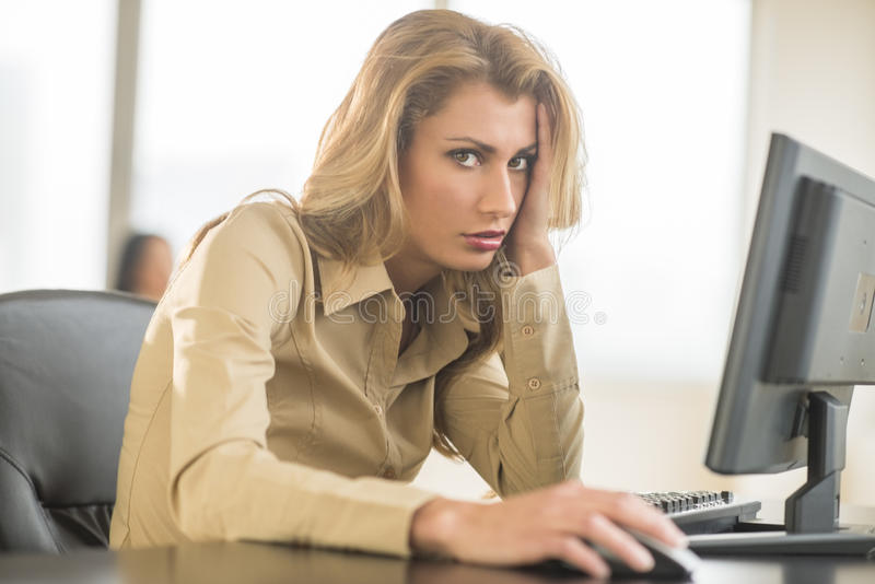 Portrait Of Irritated Businesswoman Sitting At Computer Desk