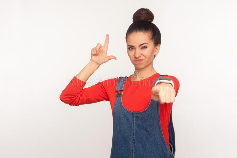 Portrait of irritated girl with hair bun in denim overalls showing loser gesture and pointing to camera, blaming for defeat. Naming you unlucky jobless. indoor royalty free stock image