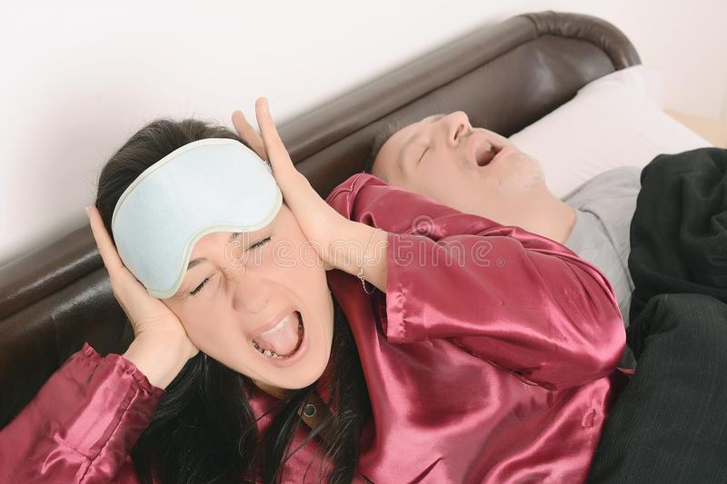 Irritated woman with anoyed man snoring on bed. Portrait of irritated women blocking ears with hands while men snoring on bed. Indoors royalty free stock photo