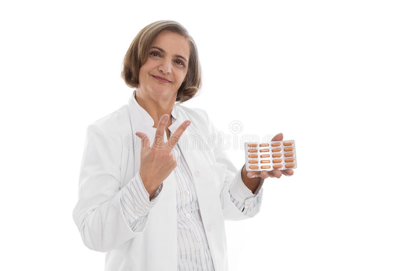 Portrait: isolated older doctor holding medicine making three fingers. Portrait: isolated older doctor holding medicine making three finger symbol royalty free stock image