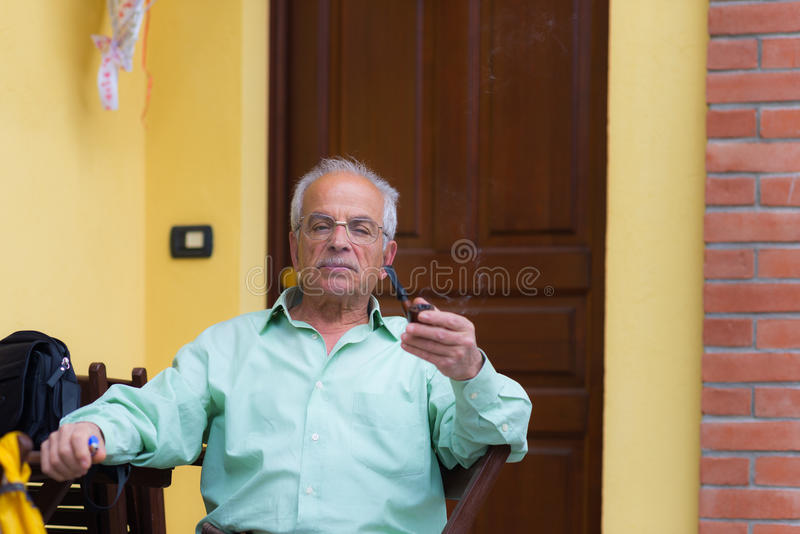 Portrait of italian senior man smoking pipe. And looking at the camera. Outdoor setting, house door and wall background stock images