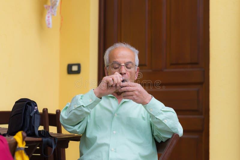 Portrait of italian senior man smoking pipe royalty free stock photography