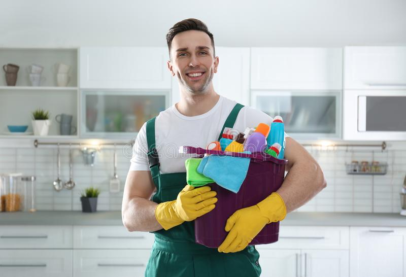 Portrait of janitor with bucket of detergents in kitchen royalty free stock photography