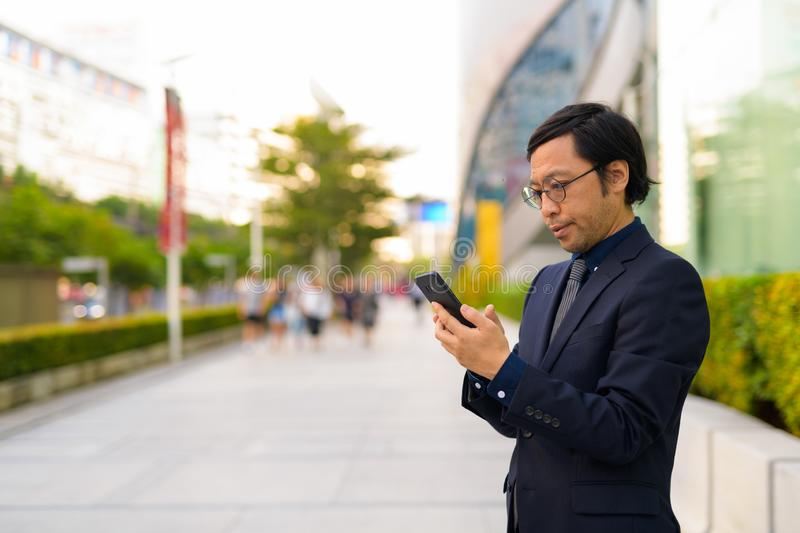 Profile view of Asian businessman using phone in the city outdoors royalty free stock photos