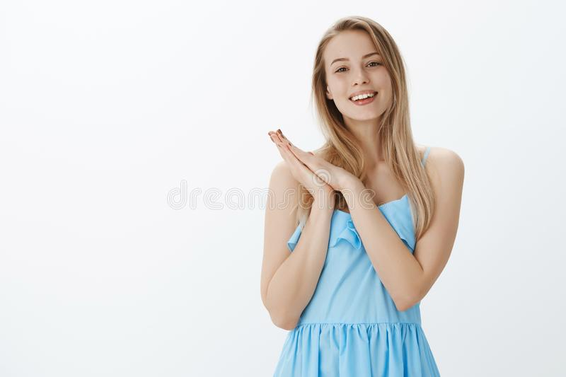 Portrait jeune de femelle avec du charme activée et sincère dans la robe bleue pressant des paumes ensemble en tant qu'ayant l'id photo stock