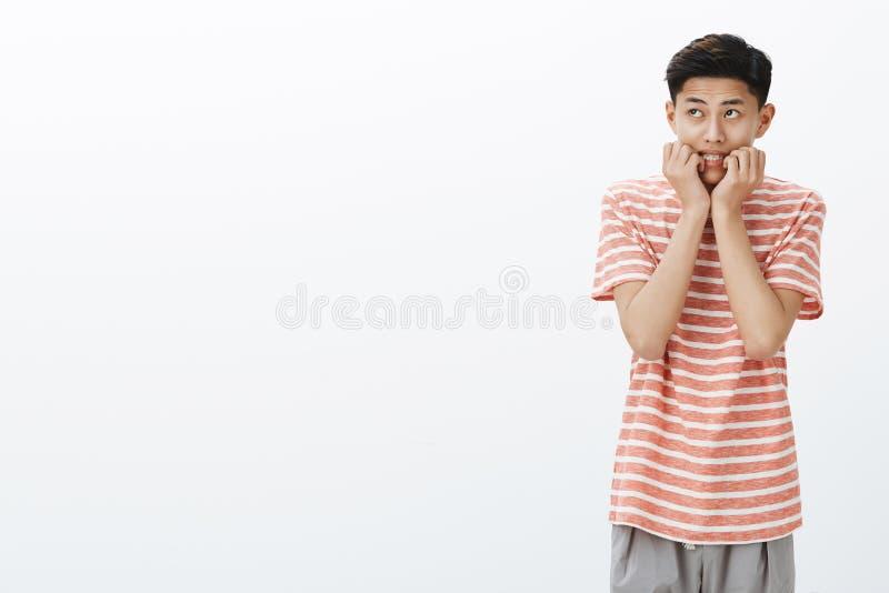 Portrait jeune de garçon asiatique nerveux et effrayé dans des doigts acérés de T-shirt rayé regardant le coin gauche supérieur p photo libre de droits