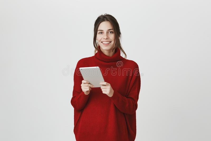 Portrait jeune de la fille enthousiaste et réussie heureuse tenant un comprimé, chandail à la mode de port d'hiver au-dessus de b image stock