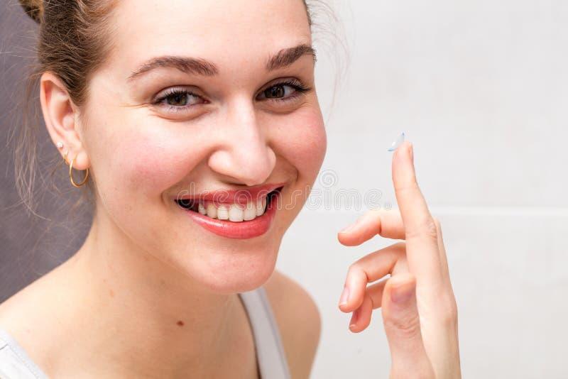 Portrait, jeune femme en bonne santé avec le sourire magnifique tenant le verre de contact photographie stock libre de droits