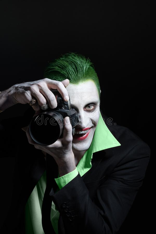 Portrait of a joker. Makeup for Halloween. Crazy image of a photographer man in a green shirt with green hair with stock photos