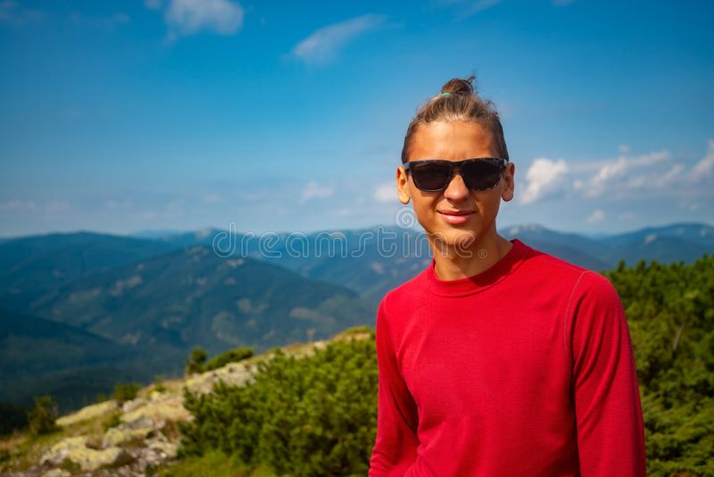 Portrait of joyful adventurer, guy teenager. Who stands in the mountains on the background of the green mountain ranges stretching to the blue horizon. Epic stock photos