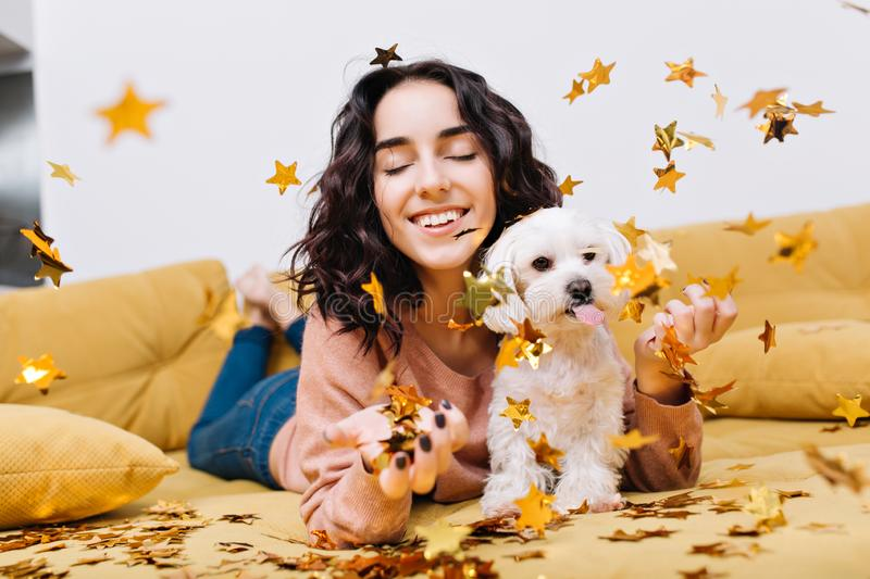 Portrait joyful amazing young woman smiling with closed eyes in falling golden tinsels. Chilling on couch with home pets royalty free stock photo