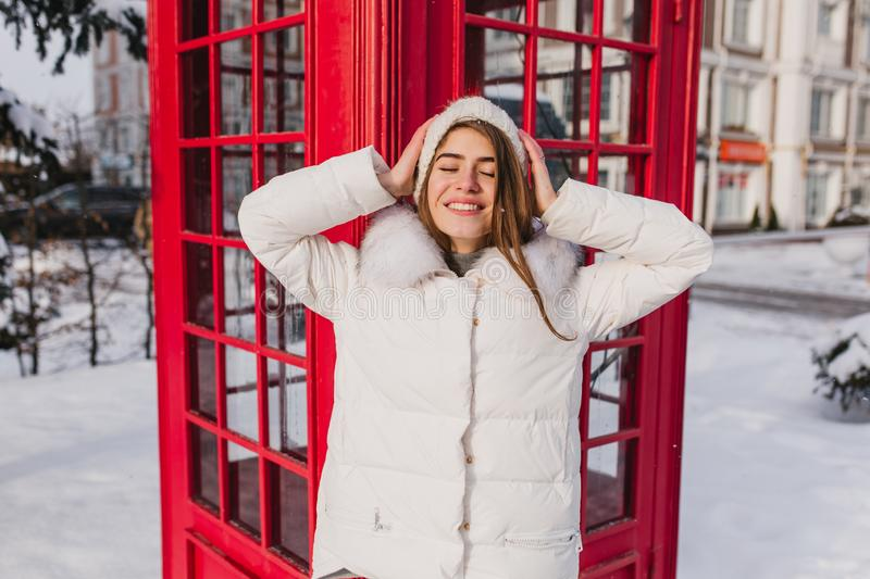 Portrait joyful amazing young woman in warm white clothes chilling on sun in frozen morning in winter time on red stock images