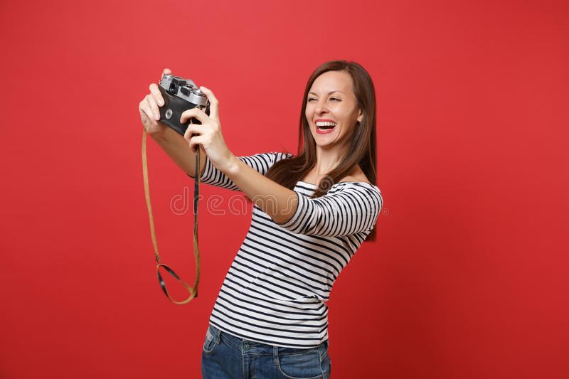 Portrait of joyful beautiful young woman doing taking selfie shot on retro vintage photo camera isolated on bright red stock photo