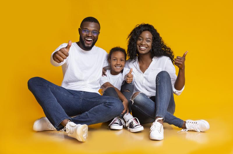 Portrait Of Joyful Black Family Gesturing Thumbs Up On Yellow Background stock photography