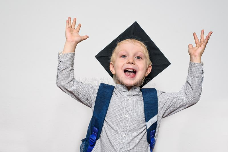 Portrait of a joyful blond boy with academic hat and a school bag. Hands up. White background royalty free stock images