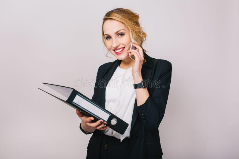 Portrait joyful blonde businesswoman talking on phone, holding folder, smiling to camera isolated on white background stock image