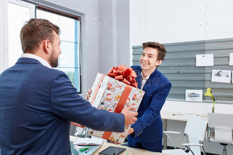 Portrait of joyful colleagues giving xmas presents to each other. Holiday concept. royalty free stock photos