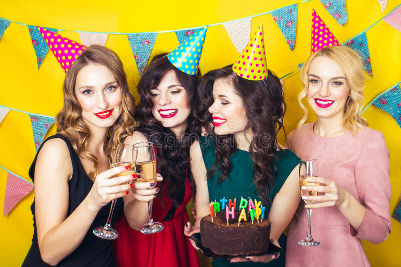 Portrait of joyful friends toasting and looking at camera at birthday party.Smiling girls with glasses of champagne stock photography