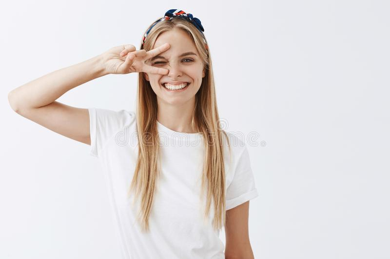 Portrait of joyful funny and playful young caucasian blond girl with headband smiling happily, showing victory or peace royalty free stock photography