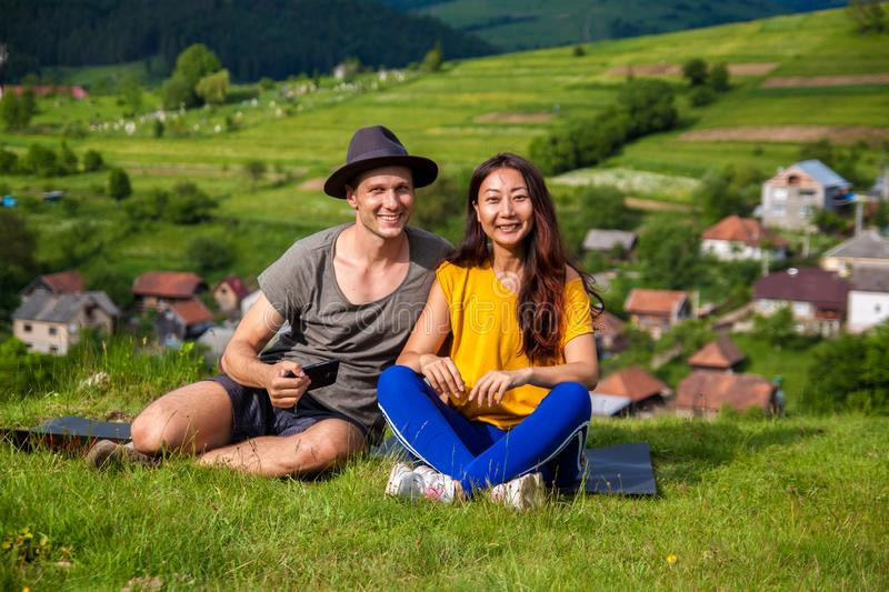 Portrait of joyful girl and boy sitting on the mountain and making selfie. Full length portrait of joyful girl and boy sitting on plaid and making selfie. They royalty free stock photos
