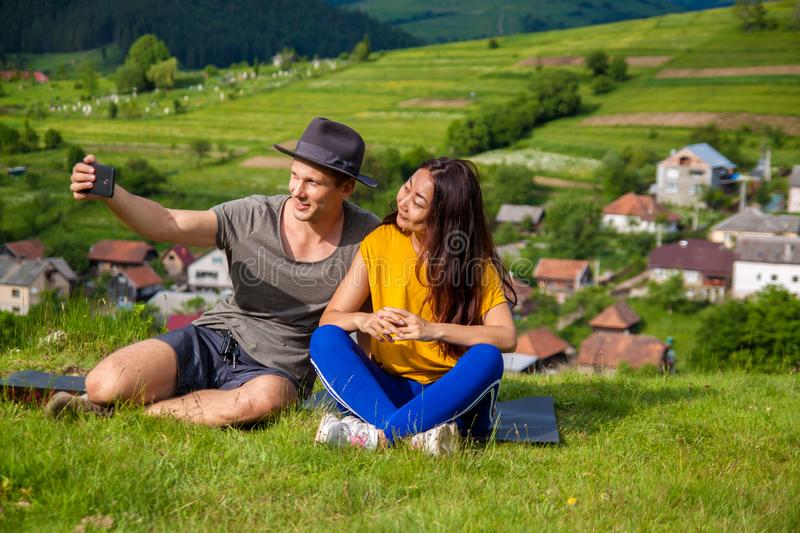 Portrait of joyful girl and boy sitting on the mountain and making selfie. Full length portrait of joyful girl and boy sitting on plaid and making selfie. They royalty free stock photo