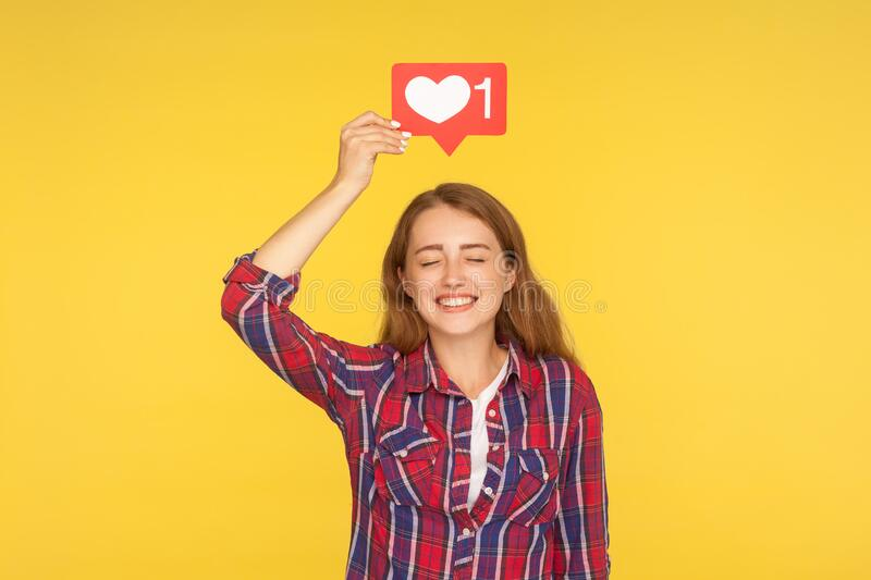 Portrait of joyful girl with closed eyes smiling and holding social media heart like icon over head, her face expressing delight. And enjoyment with internet stock photo