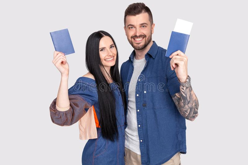 Portrait of joyful glad couple holding passport with flying tickets in hands looking at camera isolated on bright grey background stock photography