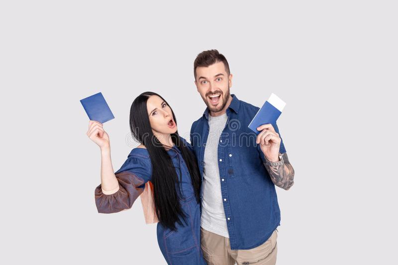 Portrait of joyful glad couple holding passport with flying tickets in hands looking at camera isolated on bright grey background royalty free stock images