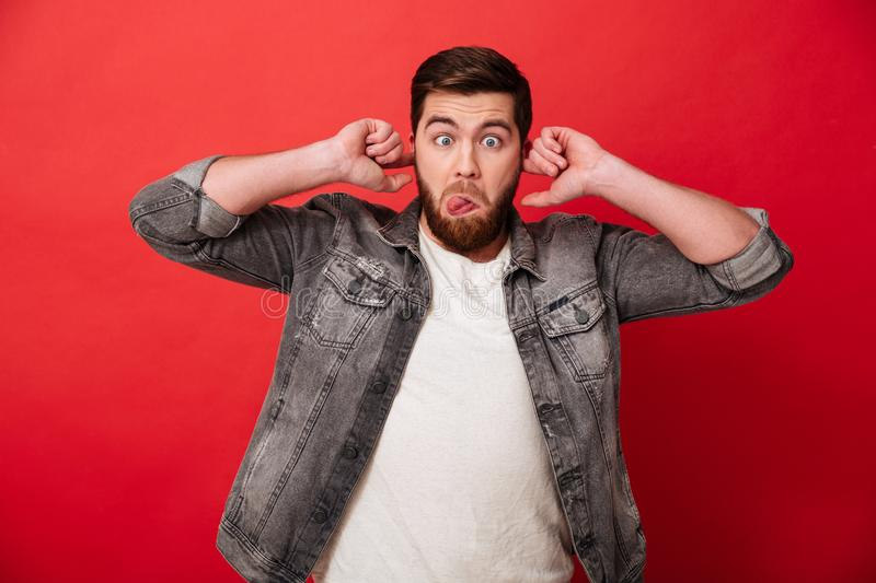Portrait of joyful guy 30s in jeans jacket fooling around with m. Aking faces and protruding ears isolated over red background royalty free stock photos